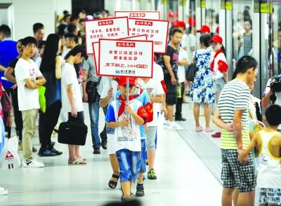 小志愿者们列队举牌倡导文明上车.记者陈亮 摄图片