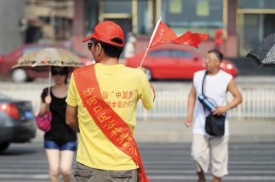 志愿者引导文明行人过马路.摄影记者曾智