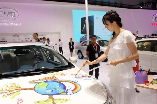 都使出了浑身解数.图为比亚迪展台,一名清新亮丽的美女车模挥高清图片