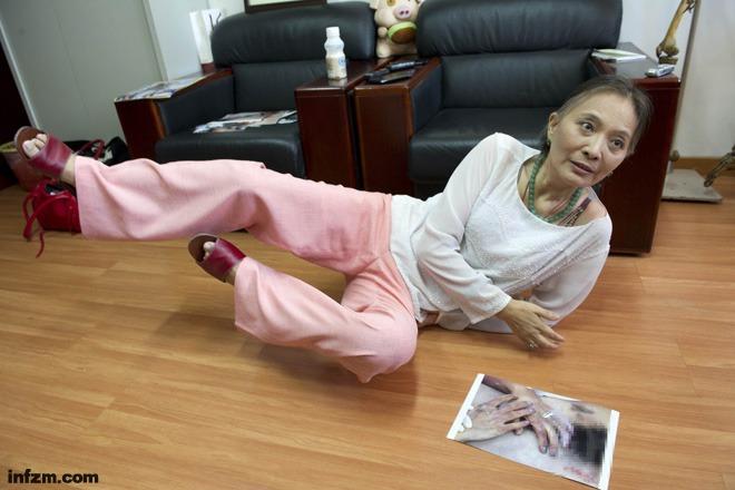 王雪梅拿着照片向记者们发表她对该案鉴定的看法,她还卧倒在地模拟马跃触电可能的各种情形。 (崔楠/图)