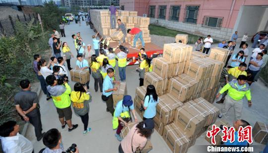 """9月6日晚,志愿者在卸下""""韩红爱心健康之家""""用品。 确・胡热 摄"""