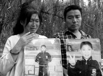 小浩的父母抱着孩子的遗像,表情痛苦。京华时报记者裴晓兰摄