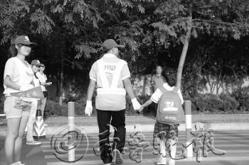 志愿者牵手护送小学生过马路。本报见习记者 田宇 摄