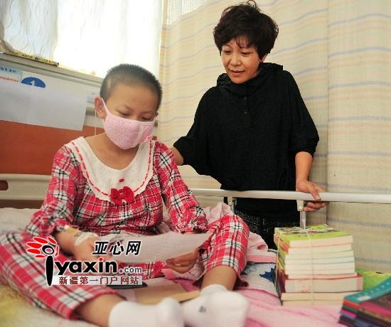 图为9月8日卞嘉敏在读一位志愿者写给她的信,病床上放着志愿者给她送来的书籍。