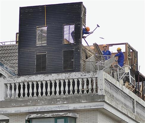 楼顶,紧贴着天台外沿而建,木质结构,共两层,9个带有铝合金窗户的鸽笼
