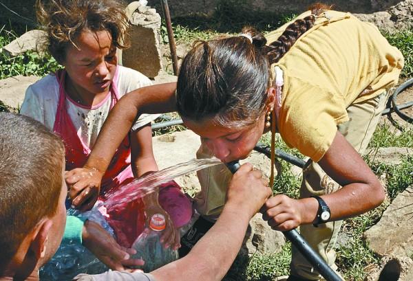 一名叙利亚难民儿童用橡胶管喝水