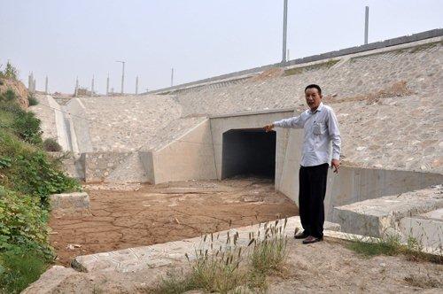 村民杜晓飞指认现场,四条排水渠汇集于此,向村里流去(贾兴鹏摄)
