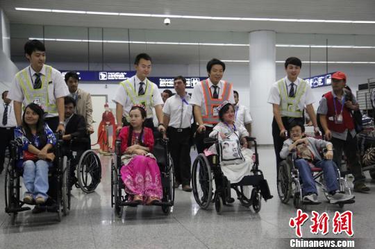 残友们在工作人员的帮助下走出到达厅. 冯明远 摄