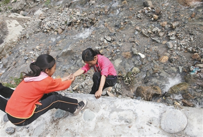 力气小的女生在力气大点的女生帮助下爬上小溪边的台阶。