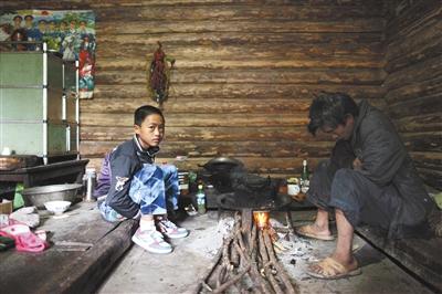同乐村,余天才坐在屋里烤火。他穿着一双新鞋,这里的孩子平均每月都要穿破一两双鞋。