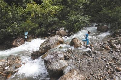 云南省迪庆藏族自治州维西县同乐村,一名小学生正跳着跨过一条湍急的溪流。当地的小学被撤并到十几公里外的镇上,孩子们上学要徒步行走十几公里的崎岖山路。上学的路上充满危险和艰辛。