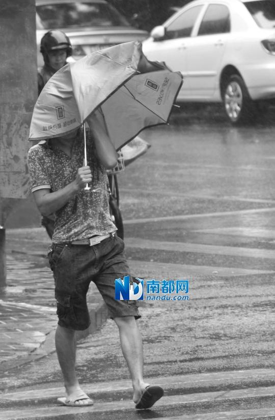 22日,汕头城区多处水浸,市民在狂风暴雨中艰难行进。新华社发
