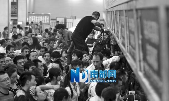 昨晚,广州东站售票厅,有性急的乘客站在栏杆上等候退票。