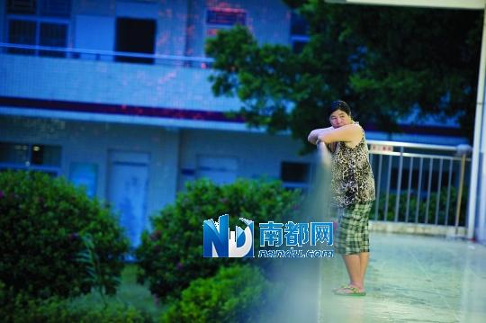 傍晚时,来自湖南的陈彩虹独自站在教室外。她平日在西涌浴场里卖游泳用品和冷饮。近日受台风影响,她被安排到小学暂住。