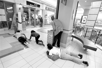 顾客在安保人员的指示下爬出购物中心。