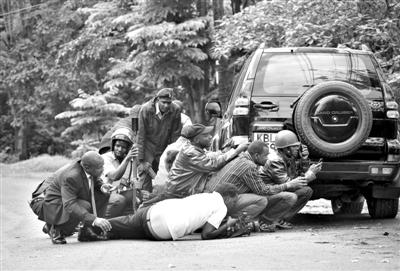 23日,肯尼亚内罗毕,遭恐怖袭击的购物中心附近,安全人员和记者躲在一辆车后。