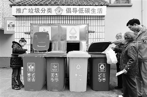 杭州开始试行生活垃圾分类处理,一位居民将已分类的垃圾投入到对应的垃圾桶内。