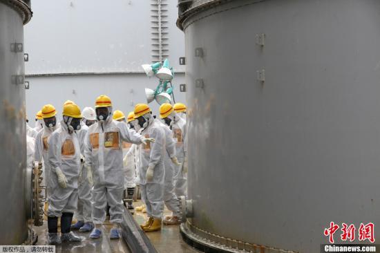 当地时间2013年8月23日,日本核监管机构工作人员身穿保护服和面具,检查福岛第一核电站污水储藏罐。