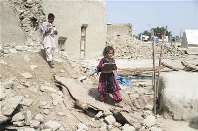 28日,巴基斯坦儿童走过地震废墟。