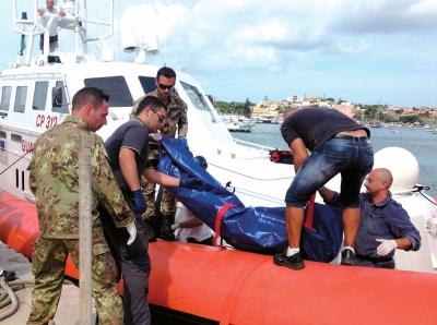 10月3日,在意大利兰佩杜萨岛港口,海岸警卫队成员搬运非法移民的尸体。新华社发