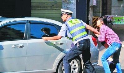男子开车违章被拦停 妻子带儿子拦交警助其逃脱