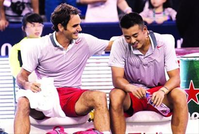 比赛获胜后,费德勒(左)搂着张择脖子称赞其表现不错。 本报记者 邵剑平 摄