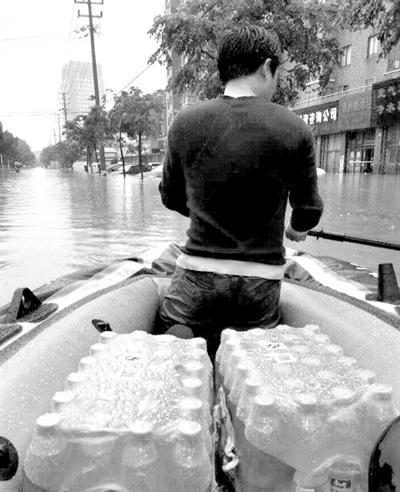 """9日,市民在余姚阳明西路的积水路段通行。台风""""菲特""""造成浙江余姚市城区大面积被淹,城市交通基本瘫痪,部分区域停电停水。 新华社记者 韩传号 摄"""