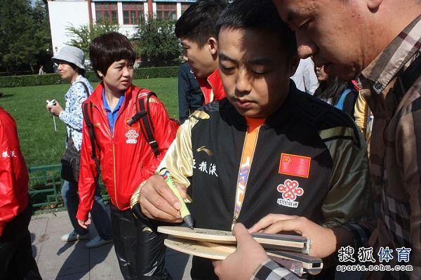 图文:中国乒乓球队去北大 刘国梁签名瞬间