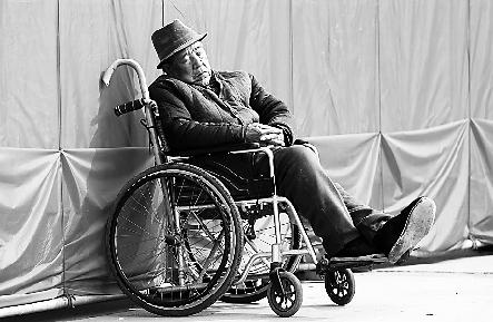一位老人在户外坐在轮椅上睡觉晒太阳