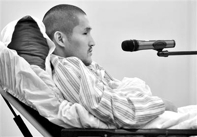 昨日庭审中,被告人冀中星躺在病床上回答法官询问。新华社发