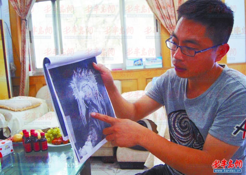 曹军拿着他曾经创作过的造型图片。