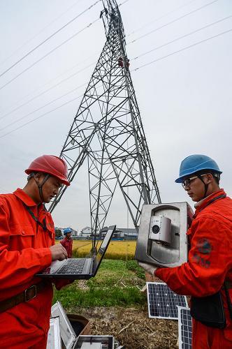 国网湖州供电公司工作人员在长兴县夹浦镇110千伏输电线路铁塔下调试
