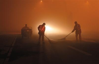 10月22日早上,长春能见度不足十米,清扫车停在环卫工身后,为其做警示保护。图/CFP