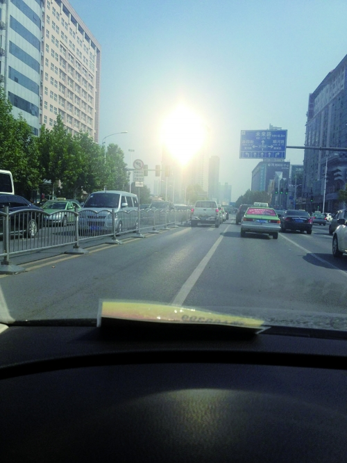 """市民驾车在金水路上由西向东行驶中,被反光的玻璃幕墙""""闪""""到眼"""