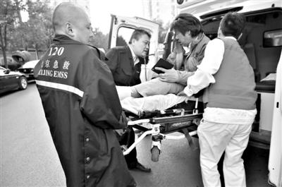 昨日下午,受伤急救车司机在派出所录完口供后,被抬上急救车离开。新京报记者 王远征 摄