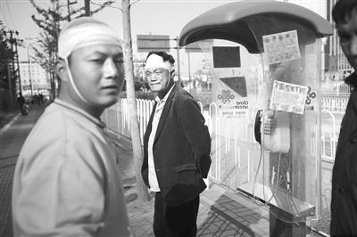 昨日,苏先生(右)和他的儿子在事发地西站南广场附近,讲述被打经过。新京报记者 王嘉宁 摄