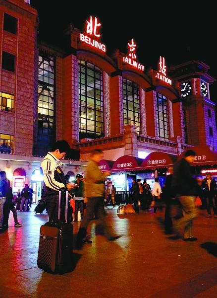 10月10日夜晚,一位年轻人在北京站等候列车。本报记者 杨杰摄