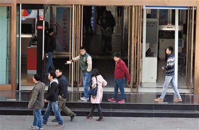 10月23日,中关村海龙大厦,多名导购站在门前揽客。中关村电子卖场虽经多番整治,但黑导购仍屡禁不绝。