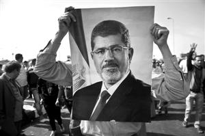 支持者手持穆尔西头像站在开罗警察学院外 新华社发