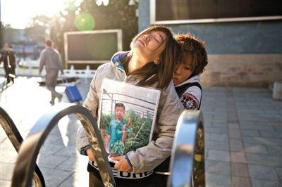 """昨日,""""小粽子""""的家人捧着他的照片站在校门口。10月23日,""""小粽子""""因在玩耍时弄伤同学被罚站,回家后跳楼身亡。新京报记者周岗峰摄"""