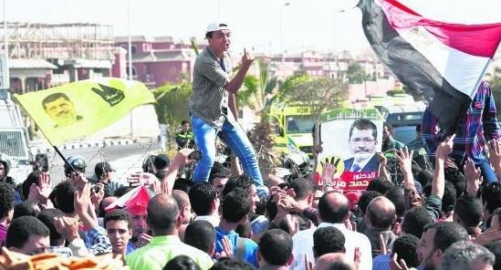 """穆尔西4日在设于开罗警察学院(背景)内的法庭受审,他的支持者举着他的头像在学院外示威,抗议当局""""非法""""审判。"""