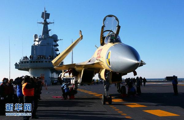 """资料图:歼-15飞机顺利在""""辽宁舰""""上着舰。 查春明 摄"""