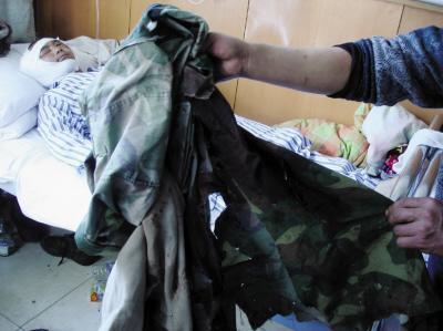 李建勇的家人展示当时被熊抓伤的外衣 照片由陈麒发提供