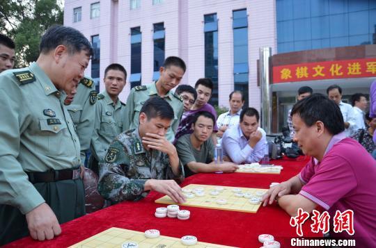 中国国际象棋大师吕钦右一与惠州军分区官兵在交流棋艺。 宋秀杰 摄