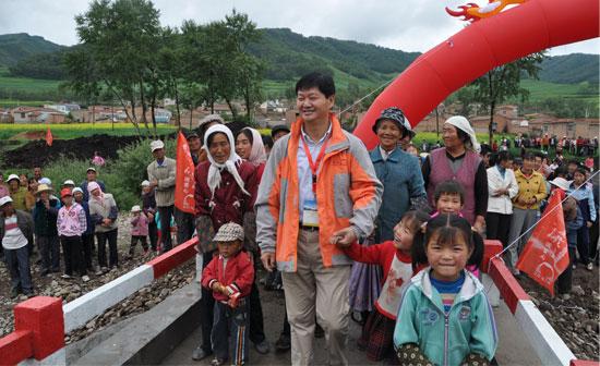 江铃集团董事长王锡高高兴地带领孩子们过桥