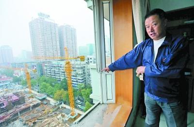 郑先生家的窗玻璃被吊车吊臂撞破。记者杨涛 摄