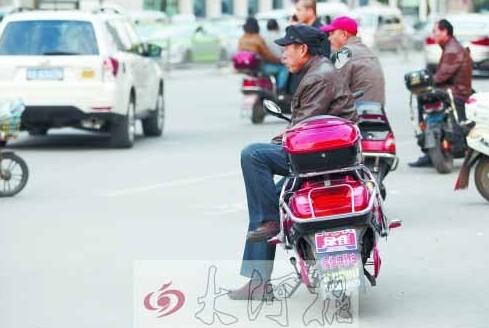 """郑州街头,多辆""""摩的""""在路口等客。"""