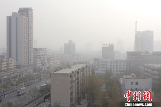 图为记者11日9时,在铁门关路和建国路交汇处的高楼上拍摄到雾霾下的梨城库尔勒。 杨厚伟 摄