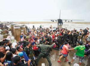 塔克洛班市灾民12日拥入机场,欲搭乘军用运输机离开灾区,他们争先恐后,与军人互相推搡