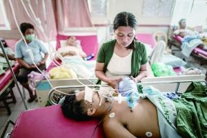 菲律宾灾区目前医疗状况堪忧。图为一名女子帮助腿部手术导致感染的丈夫呼吸。新华/法新